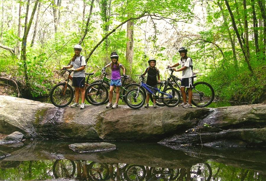 A family of 4 standing with bikes on a natural stone bridge in the woods.