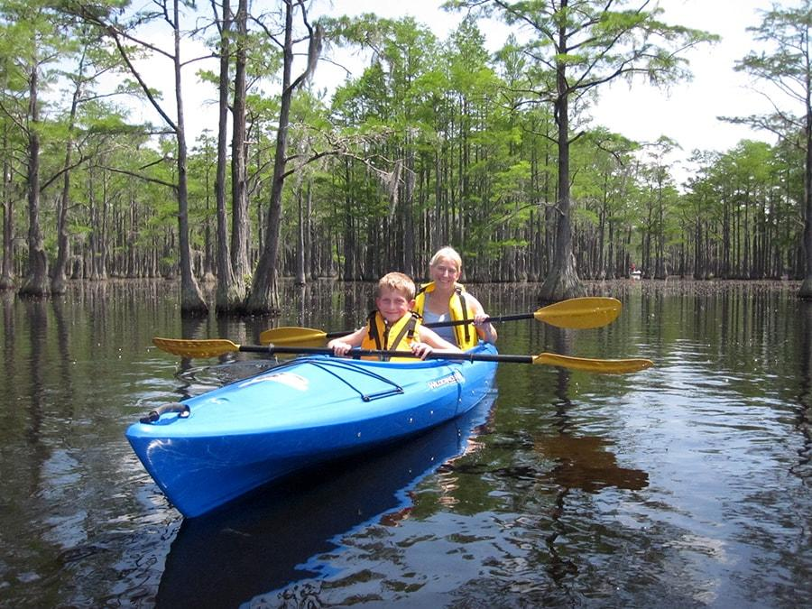 Mother and son sharing a kayak.