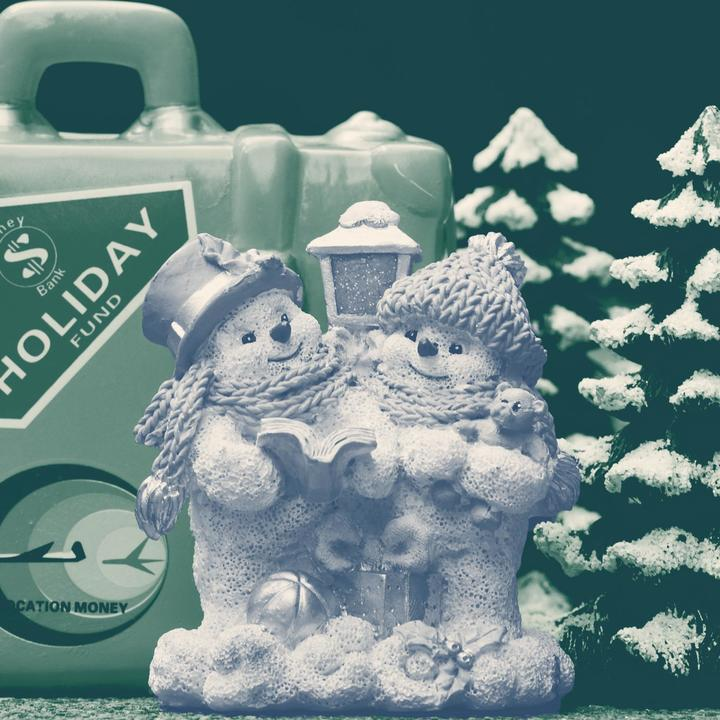 A snowman figurine in front of a toy suitcase and pine trees.